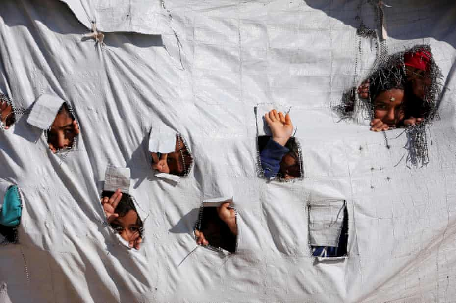 Children look through holes in a tent at al-Hawl in April