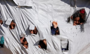 Children look through holes in a tent at al-Hawl camp in Hasaka, Syria.