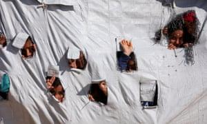 Children peering through holes in a tent in al-Hawl camp