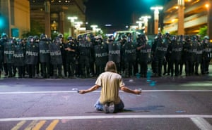 Phoenix, Arizona, US A protester sits on Second Street in front of a row of riot police trying to clear the area around the Phoenix Convention Center after President Donald Trump spoke at a rally in the city