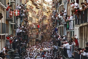 People crowd onto their balconies to watch the horde of runners in the street