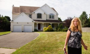 Margaret Besen stands in front of the former Besen family home, now unoccupied in Commack, Long Island.