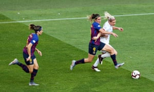 Eugenie Le Sommer of Olympique Lyonnais dribbles the ball away from Barbara Latorre of Barcelona.
