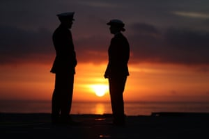 Members of the crew of HMS Queen Elizabeth stand on the deck at sunrise ahead of the ship's arrival in Portsmouth