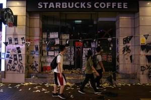 People walk past a vandalised Starbucks cafe in Wanchai district in Hong Kong.