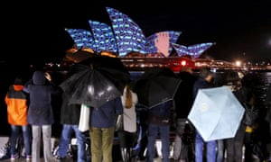 Spectators in the rain watch projections on the roof of the Sydney Opera House on the opening night