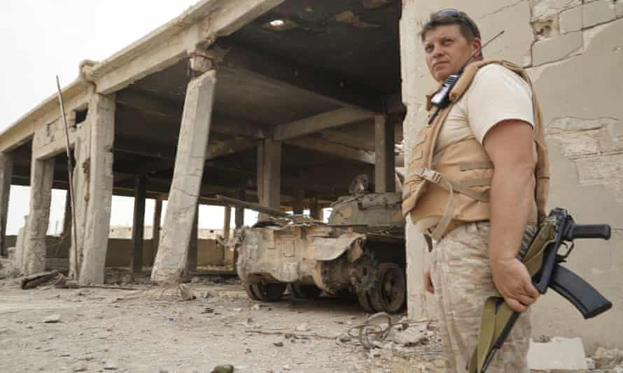 A Russian soldier stands in front of a destroyed tank factory operated by Isis militants.