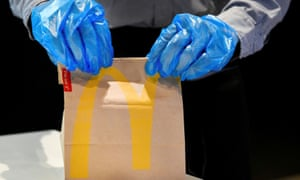 An employee wearing protective gloves handles an order at a prototype location of fast food giant McDonald's for restaurants which respect the 1.5m social distancing measure, amid the coronavirus disease (COVID-19) outbreak, in Arnhem, Netherlands, May 1, 2020. REUTERS/Piroschka van de Wouw
