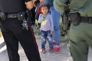 McAllen, Texas A Mission Police Dept. officer (L), and a US Border Patrol agent watch over a group of Central American asylum seekers