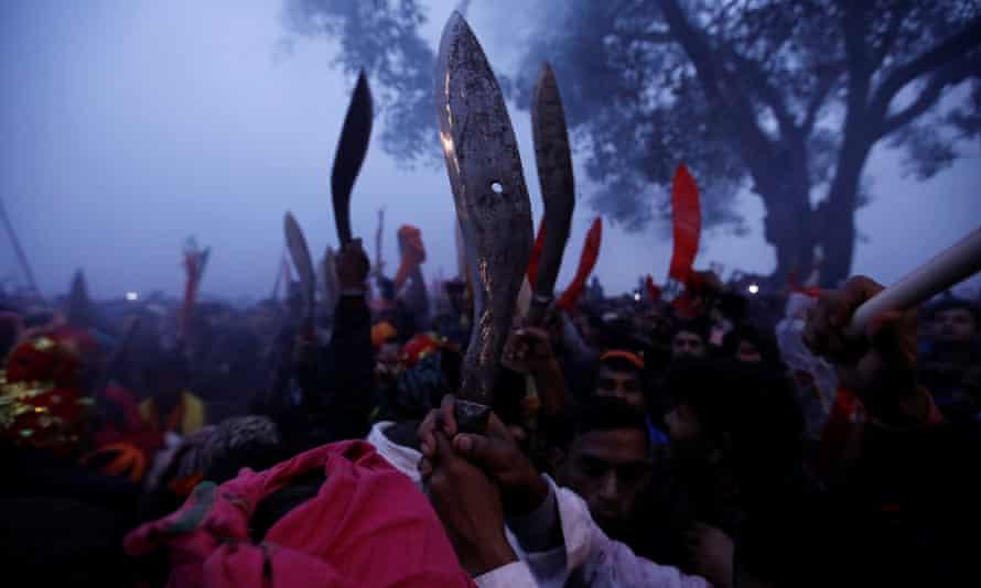 Devotees raise their sacrificial blades known as khukuris as the festival begins.
