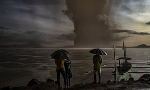 Residents look on as Taal volcano erupts on Sunday in the Philippines