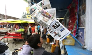 An Afghan boy reads a local newspaper at a newsstand in Kabul.