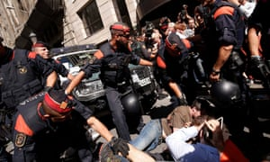Catalan police officers try to disperse protesters in Barcelona