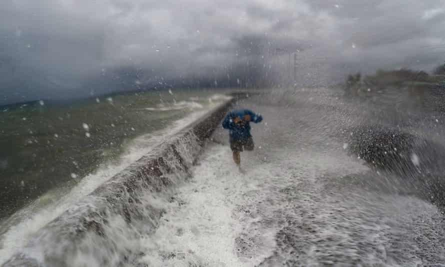 Waves spill over a wall in the city of Legaspi in Albay province, south of Manila, as typhoon Melor approached the city.