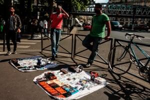 People walk past men selling items in a street in La Chapelle