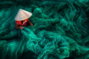 In a small fishing village in southern Vietnam, a woman creates a bright green handmade fishing net.