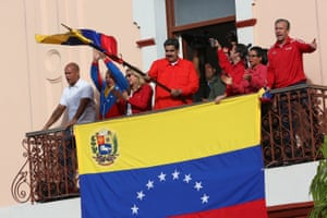 President of Venezuela Nicolás Maduro (C) waves a national flag as he is escorted by (FROM L TO R) Hector Rodriguez, Governor of Miranda; Diosdado Cabello, President of National Constitutional Assembly; Cilia Flores, First Lady; Major Erika Farias and Economic Vice President Tareck El Aissami at the Balcón del Pueblo of the Miraflores Government Palace