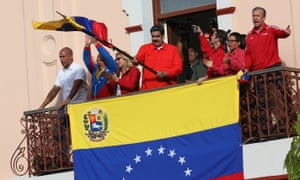 Nicolás Maduro waves a national flag at the Government Palace in Caracas