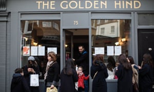 People stand outside a pub in Marylebone, London