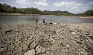 A man and a boy try to fish while standing on the dry shores of the almost empty La Plata reservoir in Toa Alta, Puerto Rico.