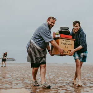 Chef Charlie Hodson and author Patrick Barkham move their cooking utensils to another part of the sandbank as the tide comes in. Norfolk, UK.