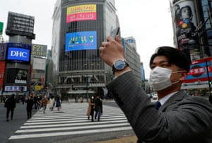 A man wearing a protective face mask, takes a selfie at Shibuya Crossing in Tokyo, Japan