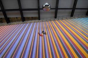 London, UK. Visitors lie on a huge carpet as they view a swinging pendulum suspended from the roof which forms part of the new installation One Two Three Swing! by Danish art collective SUPERFLEX, at the Tate Modern