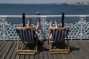 Two people look out to sea from deck chairs in Brighton