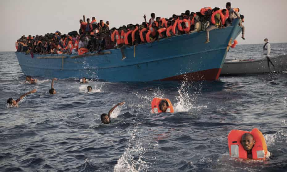 Migrants, most from Eritrea, jump into the water during a rescue operation off Libya in August.