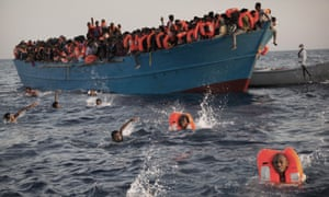 Migrants from Eritrea jump into the sea from a crowded wooden boat during a rescue operation