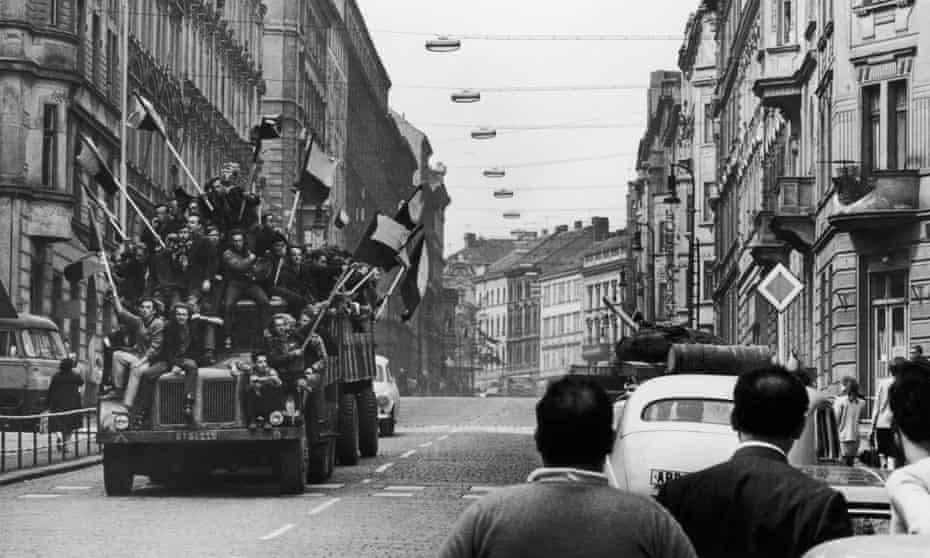 August 1968: a truck with Czech civilians waving flags drives past a Soviet tank in Prague.