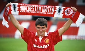 Roy Keane holds up a Manchester United after signing in 1993