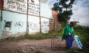 A resident sits in a Brazil flag in the mostly demolished Vila Autodromo favela in Rio de Janeiro