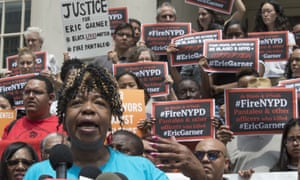 Gwen Carr, whose son Eric Garner was killed by an NYPD officer, is surrounded by supporters as she speak during a news conference outside City Hall in New York on Tuesday.