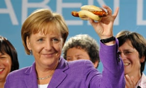 Germany's chancellor, Angela Merkel, holds aloft a Thüringer Rostbratwurst a few years ago.