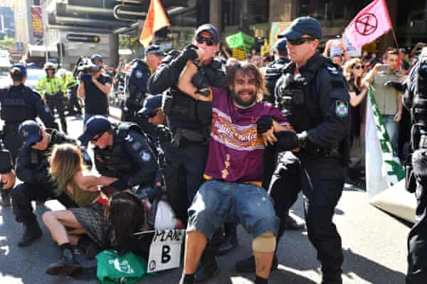 Police arrest Extinction Rebellion protesters after they blocked the corner of Edward and Queen streets in Brisbane.