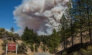 A large smoke plume from the Carr fire rises behind the hillsides leading to the mountain community of Lewiston California wildfires, USA - 02 Aug 2018