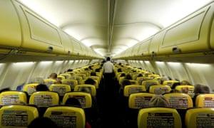 A cabin crew member serves passengers onboard a Ryanair flight