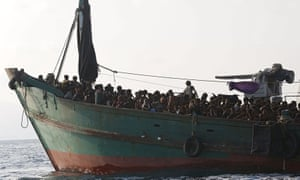 Migrants are seen aboard a boat tethered to a Thai navy vessel in waters near Koh Lipe island in May. Amnesty International says Australia's policy of boat turnbacks has acted as an example for other countries.