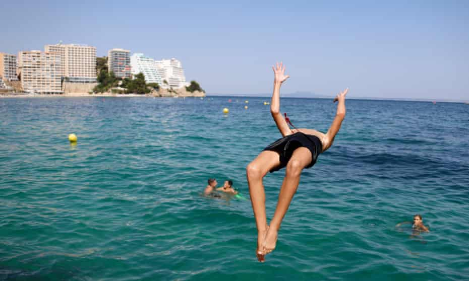A boy jumps into the sea from the rocks of Magaluf beach, Mallorca.