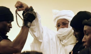 Former Chadian president Hissène Habré (centre) is escorted into the courtroom by prison guards for the first proceedings of his trial in Dakar on 20 July 2015.