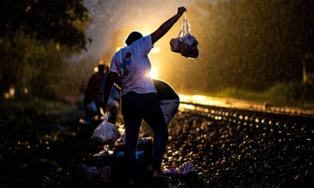 A volunteer distributes bags of food among migrants as they travel through Mexico to the US on a train known as 'La Bestia' in Veracruz state, Mexico.