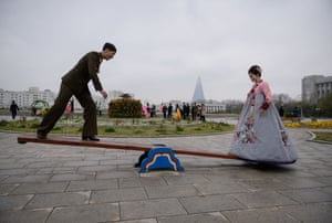 A bride and groom pose on a seesaw during a wedding photoshoot at a park