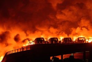 Fire and smoke are seen after explosions at a warehouse on late Wednesday in Binhai New Area