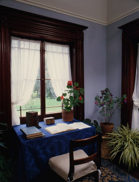 an old fashioned desk with an open book and pot of geraniums on it, in front of a window