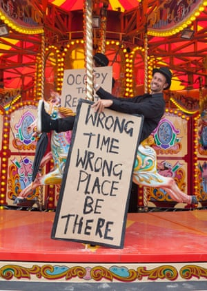 A man holds a protest sign on the carousel.