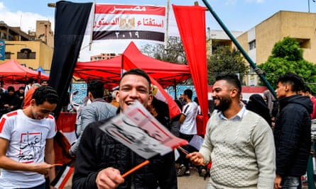 Egyptians wave flags stating 'Do the right thing' as part of the campaign to get voters to back the changes.