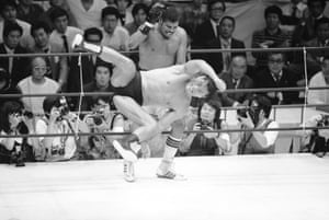 Leon Spinks evades a flying kick by the Japanese professional wrestling champion Antonio Inoki in the sixth round of their scheduled 12-round boxing vs wrestling match in Tokyo on 9 October 1986. Inoki pinned Spinks to the mat for five seconds for the win.