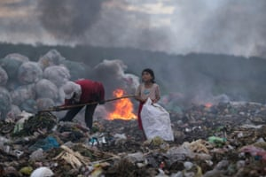 """Winner of Ciwem environmental photographer of the year 2017: Quoc Nguyen Linh Vinh for 'The hopeful eyes of the girl making a living by rubbish' Vinh's winning photo is a poignant image of a child and her mother collecting waste. Vinh said """"The child was happy, looking at the dark clouds and chatting to her mother. This was so touching. She should have been enjoying her childhood and playing with friends rather than being there."""""""