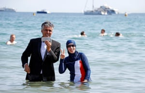 Businessman and political activist Rachid Nekkaz poses with Karima, wearing a full-body burkini swimsuit, on a beach in Cannes after his call to support the wearing of burkinis.